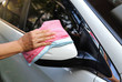 Closeup of rear view mirror of white car cleaning, polishing by woman owner's hand with pink and blue microfiber cloths.