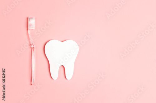Valokuva  White paper tooth with toothbrush on pink background