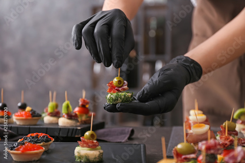 Fototapeta Chef preparing tasty canapes for serving obraz