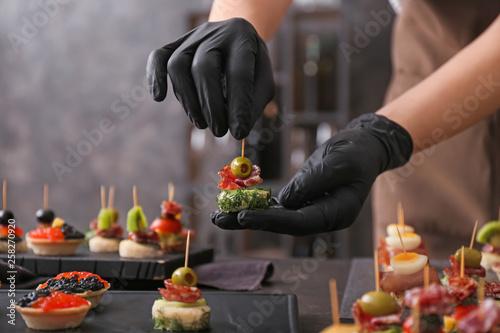Fototapeta Chef preparing tasty canapes for serving obraz
