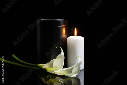 Fotografía  Mortuary urn, burning candle and flowers on dark background
