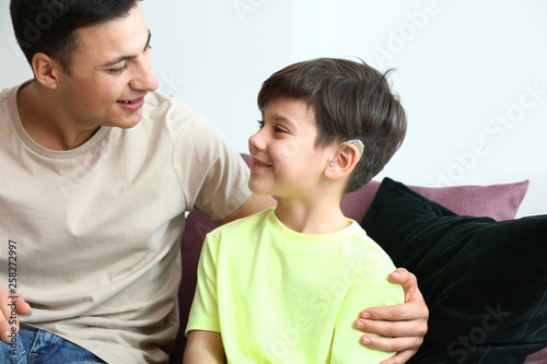 Young man and his son with hearing aid at home Canvas-taulu