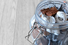 Potpourri Blue Colour In A Glass Jar With Metal Clasp On A Grey Wood Background