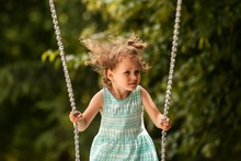 Happy Child Girl On Swing On Warm And Sunny Day Outdoors. Little Kid Playing On Nature Walk In Playground In Park, Cute Blond Girl Swinging High, Active Summer Leisure For Kids, Joyful Holidays