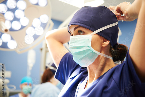 Fotografiet  Side view of young female surgeon tying her surgical mask
