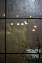 Rain Drops On Window Glass Outside At Night. Green Blurred Lights. Surface Of Wet Glass. Water Splash. Bokeh Lights Bokeh During The Rain.