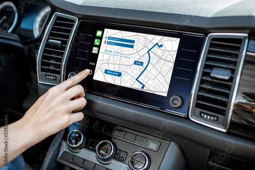 Touching a monitor with navigation map of the modern car, close-up view Fototapeta