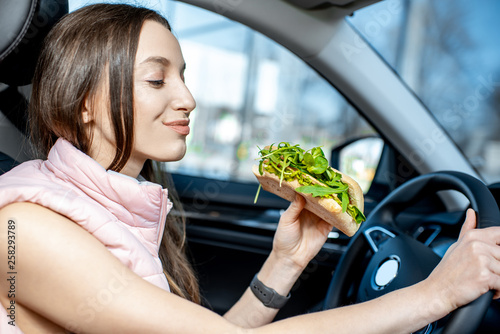 Fototapeta Young and cheerful woman in sportswear eating healthy sandwich with salad while driving car in the city obraz
