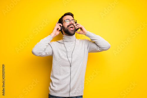 Man with beard and turtleneck listening to music with headphones - 258293909