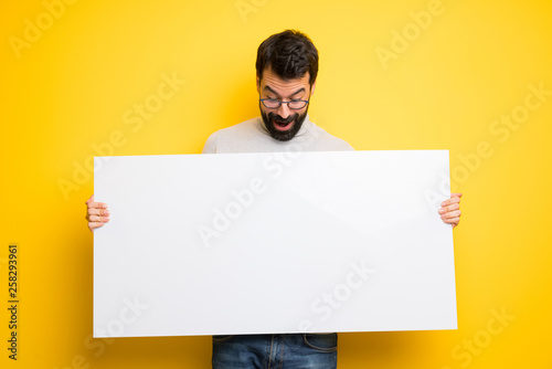 Fotomural  Man with beard and turtleneck holding a placard for insert a concept