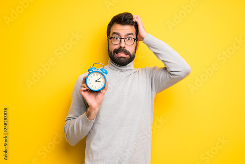 Fotografía  Man with beard and turtleneck restless because it has become late and holding vi