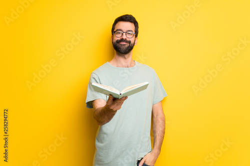 Fotografía  Man with beard and green shirt holding a book and giving it to someone