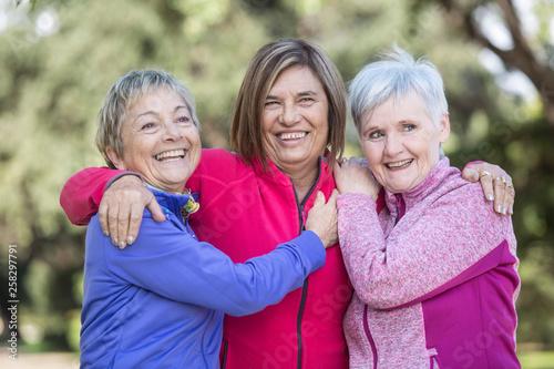 Foto trio di  di amiche mature ridono felici vestite con tute colorate al parco