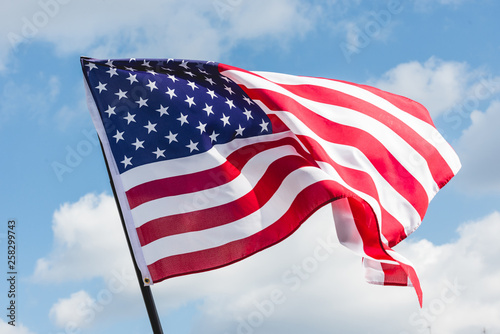 Obraz low angle view of stars and stripes on american flag against blue sky - fototapety do salonu