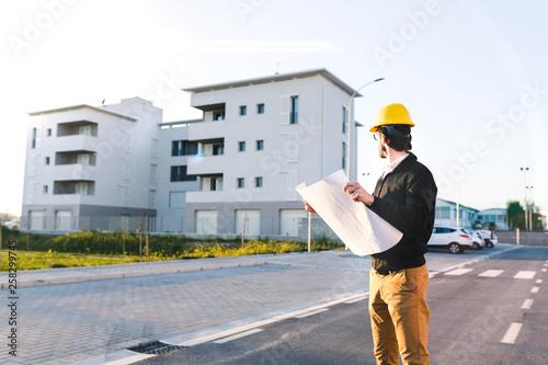 Fotografie, Obraz Giovane Architetto di spalle con giacca nera e pantaloni gialli valuta la correttezza del disegno del progetto sul foglio di carta prima di procedere con l'ispezione dei lavori
