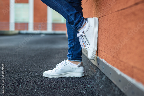 Woman with leather white sneaker leaning wall in city, close-up side view Obraz na płótnie