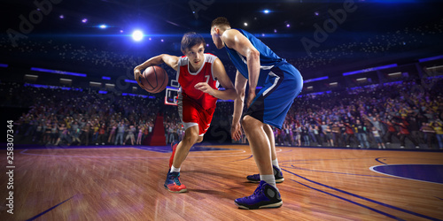 Photo Basketball player n action. around Arena with blue light spot