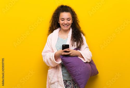 Fototapeta Teenager girl in pajamas sending a message with the mobile obraz na płótnie
