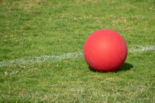 Red Playground Kickball Ball On The Green Grass In The Bright Sunshine. Summer Fun.