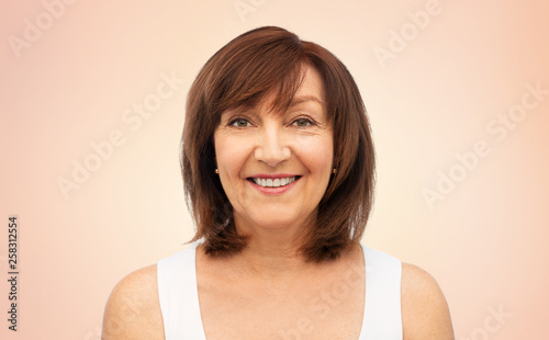 Fotografie, Obraz  beauty and old people concept - portrait of smiling senior woman over beige back