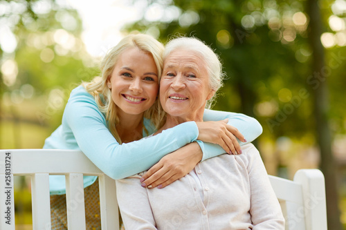 Fototapeta family, generation and people concept - happy smiling young daughter with senior mother sitting on park bench and hugging obraz