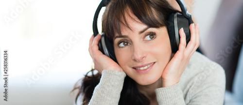 Obraz Jeune femme écoutant de la musique avec un casque audio - fototapety do salonu