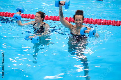 Cuadros en Lienzo  Multiracial couple attending water aerobics class in a swimming pool