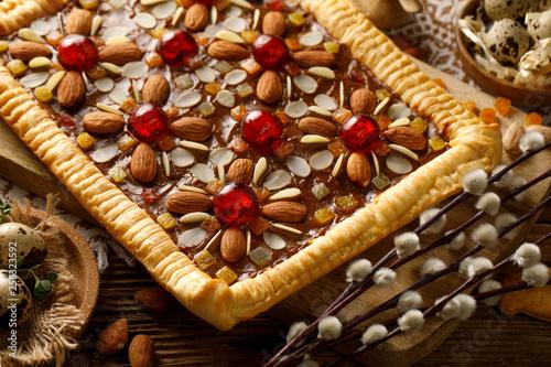 Mazurek, tradycyjne polskie ciasto wielkanocne z kruchego ciasta, karmelowej krówki, kandyzowanych owoców i migdałów, widok z góry, zbliżenie. Wielkanocna uczta