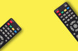 canvas print picture - Pair of black plastic remote controls for different multimedia devices on yellow background with copy space for your text. Top view