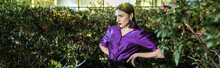 Panoramic Shot Of Elegant Young Woman In Purple Blouse Standing With Arms Akimbo In Orangery