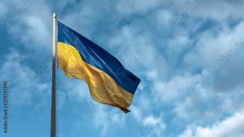 Fotografia  Blue and yellow Ukrainian national flag on a flagpole against a blue sky in the sunny day, view from below, blurred background