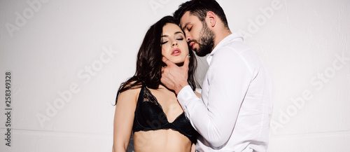 Fotografie, Obraz  panoramic shot of handsome man touching face of sexy woman in black bra standing