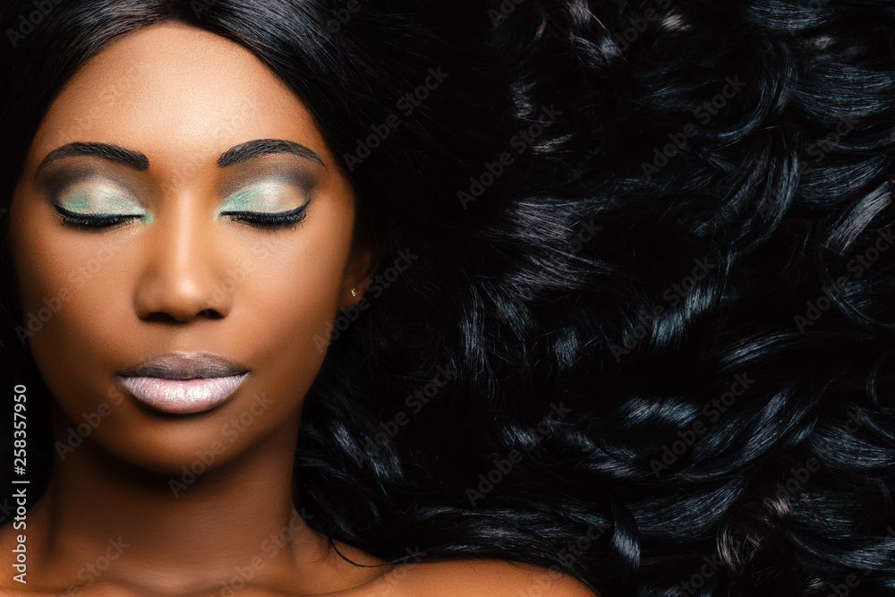 Fototapeta Beauty portrait of african woman showing long hair with smooth waves.