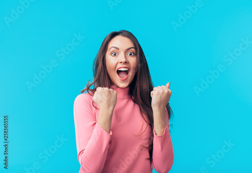 Fényképezés  Happy excited woman celebrate success isolated on blue background