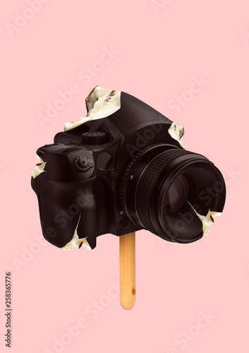 A natural icecream. An alternative view of sweets. A camera formed creamy ice on the wooden stick on trendy coral background. Photography or food concept. Modern design. Contemporary art collage.