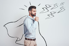 I Am Enough Strong! Confident And Attractive Young Man Wearing A Drawn Cape Showing Gesture Of Success While Standing Against Grey Background With Illustration Of The Lightning Bolts