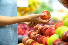 Woman's Hand Choosing Red Apple In Supermarket