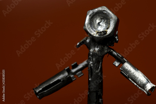 Fotografie, Obraz  Small welded figurine of scrap metal and screw bolt as a head with wondering att