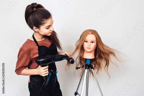 woman hairdresser student studying on mannequin head.