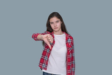 Young Teen Girl Shows Thumb Down, Gray Wall Background