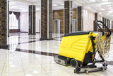 Cleaning machine in the empty office lobby. Yellow vacuum equipment for cleaning is on the shiny marble floor. Concept of professional cleaning and care service.