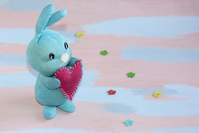 Blue Cute Bunny With A Red Heart In Its Paws On A Pink- Light Blue Background. Handwork.