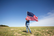 Man Holding American Flag On Field In Remote Landscape