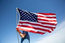 Man Holding American Flag Under Blue Sky