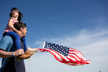 Man With Daughter And American Flag Under Blue Sky