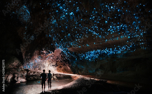 Stampa su Tela Under a glow worm sky - couple shining a light into Waipu cave filled will glow