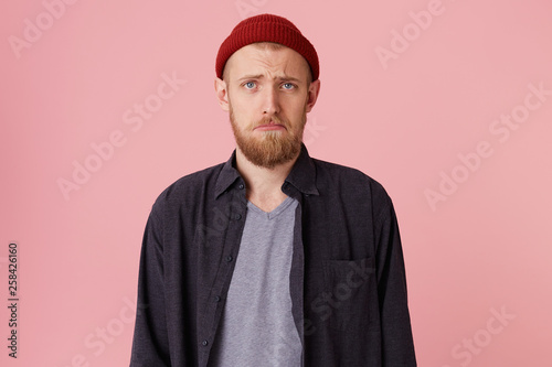 Fotografie, Obraz  Close up of a sad bearded man about to cry, in blak shirt and t-shirt, with red hat, looking at the camera and frowning over pink background