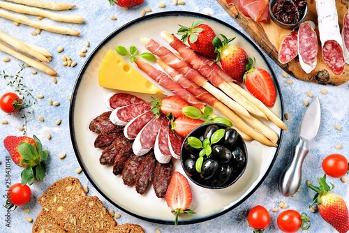 Antipasti snacks - sausage, homemade grissini with jamon, olives, strawberries, capers, cherry tomatoes, white wine, dried tomatoes and more Fototapet