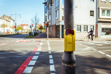 Pedestrian Crossing Button With Blurred People Crossing The Road At The Crosswalk, Close Up Yellow Crossing Button On The Street In Germany, Krefeld