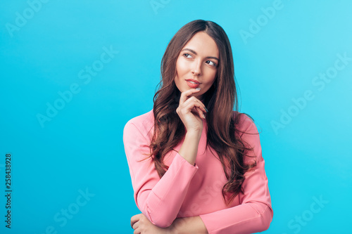 Portrait of thoughtful wondering woman looking sideways isolated over blue backg Fototapet